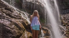 Girl standing under waterfall getting wet Stock Footage