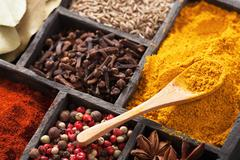 Spices in box: pink black pepper, paprika powder, curry, bay leaf; anise; clo Stock Photos