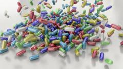 Pills drugs capsules falling on white table counter top slow motion closeup DOF Stock Footage