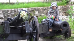 Cute little boy holding a colored ball sitting on war cannon  Stock Footage