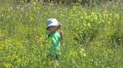 Gorgeous scenery, lovely child playing with  flower in blossom field, try cut Stock Footage