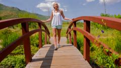 Young girl walking across bridge on summer day Stock Footage