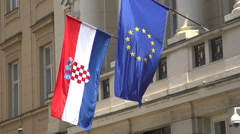 Croatian and European flags blowing in breeze in slow motion Stock Footage
