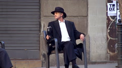 Stylish Spanish elderly man with a cigarette is resting on a bench Stock Footage