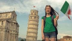 A young tourist smiles to camera in front of The Leaning Tower of Pisa Stock Footage