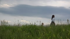 Baby son walking to young mother on top hill, evening skyline Stock Footage