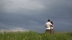 Young couple embracing together and admiring the horizon line Stock Footage
