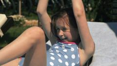 Little girl relaxing by the pool in slow motion Stock Footage