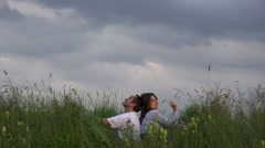 Stock Video Footage of Dreaming couple relaxing on hill peak, close blue sky, falling in love