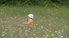 Little boy walking in blossom spring field to his mother arms Stock Footage