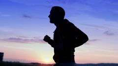 Silhouette of young man jogging during sunset HD Stock Footage