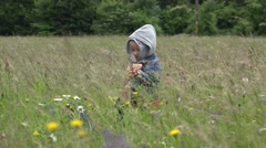 Adorable baby holding parent hand playing in blossom meadow, windy whether 4K Stock Footage