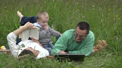 Family relaxing in nature, mother reading a book, father, baby looking laptop Stock Footage