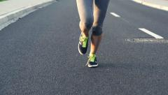 Woman jogging on asphalt road HD Stock Footage