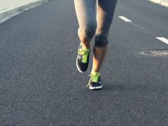 Woman jogging on asphalt road NTSC Stock Footage