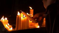 Prayer candles being placed in slow motion Stock Footage