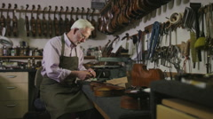 Craftsman in his workshop, making and restoring violins - stock footage