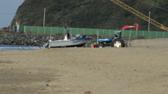 A Tractor Tows a Boat Off A Beach Stock Footage