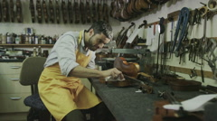 Stock Video Footage of Craftsman in his workshop, making and restoring violins
