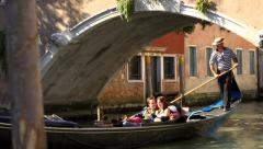Gondolier punting down a Venice canal - with young couple - stock footage