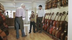 Father and son shopping together, looking at violins in a musical store Stock Footage