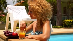 Young Woman Eating Fruits in the Pool. Hot Summer Day. Stock Footage