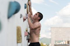 Struggling to reach handhold on climbing wall Stock Photos