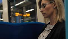 Woman uses digital tablet on city train Stock Footage