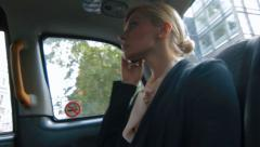 Businesswoman on phone in taxi in London Stock Footage