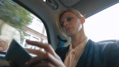 Businesswoman using her digital tablet in a taxi in London Stock Footage