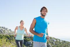 Stock Photo of Fit couple jogging through countryside