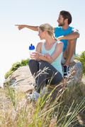 Fit couple taking a break at summit - stock photo