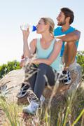 Fit couple taking a break at summit looking at the view - stock photo