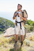 Handsome hiker holding binoculars on mountain trail - stock photo