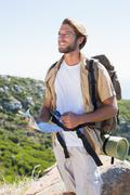 Stock Photo of Handsome hiker holding map and compass at mountain summit