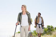 Attractvie hiking couple walking on mountain trail Stock Photos
