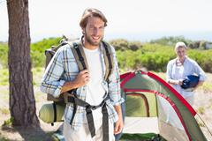 Stock Photo of Attractive man smiling at camera while partner pitches tent