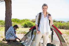 Stock Photo of Attractive blonde smiling at camera while partner pitches tent