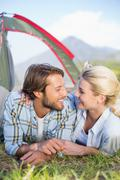 Attractive couple lying in their tent about to kiss - stock photo