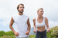 Attractive couple jogging on mountain trail - stock photo