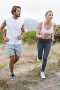 Attractive couple jogging on mountain trail Stock Photos