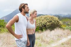 Stock Photo of Attractive fit couple standing on mountain trail
