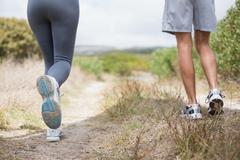 Fit couple jogging on mountain trail - stock photo