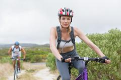 Fit couple cycling on mountain trail - stock photo