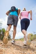 Fit couple running up mountain trail - stock photo