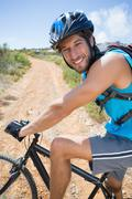 Fit man cycling up mountain trail smiling at camera - stock photo