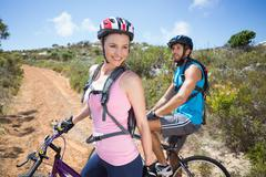 Stock Photo of Fit couple cycling up mountain trail smiling