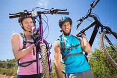Stock Photo of Fit couple walking down trail smiling at camera holding mountain bikes