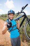 Fit man walking down trail holding mountain bike smiling at camera - stock photo