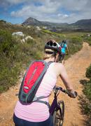Stock Photo of Fit couple cycling on mountain trail